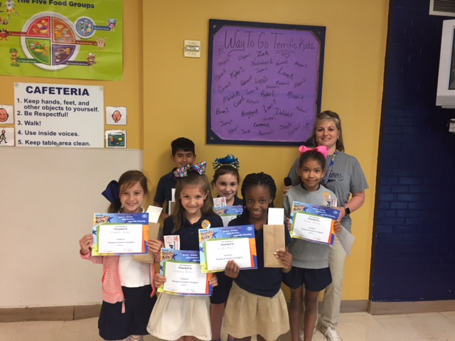 pictured are students with their terrific kids certificates smiling with principal